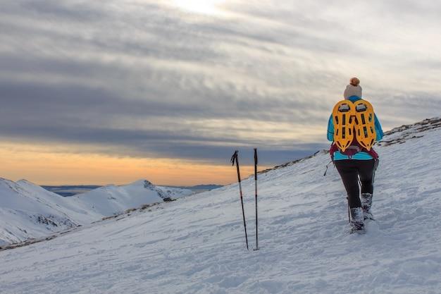 Meisje met rugzak in de bergen met sneeuw. lifestyle concept Premium Foto