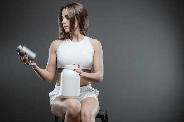Meisje met supplement wei-eiwit shake poeder Premium Foto