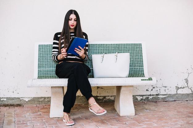 Meisje met tablet op bankje Gratis Foto