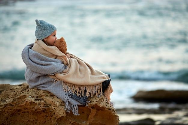 Meisje met teddybeerzitting op strand Premium Foto