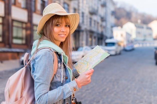 Meisje met trendy look locatie kaart in de hand kijken naar de camera Gratis Foto
