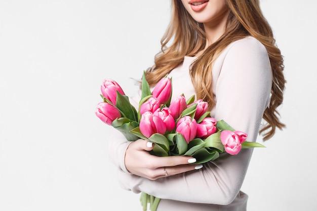 Meisje met tulpen die zich op grijs en het glimlachen bevinden Premium Foto