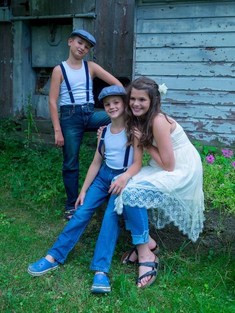Meisje met twee broers zittend op een steen in een boerderij omgeven door hekken en groen Gratis Foto