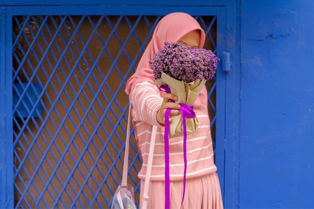 Meisje met violet boeket op blauwe muur Premium Foto