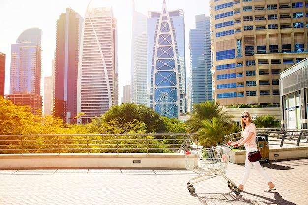 Meisje met winkelwagentje loopt over de brug voor wolkenkrabbers Gratis Foto