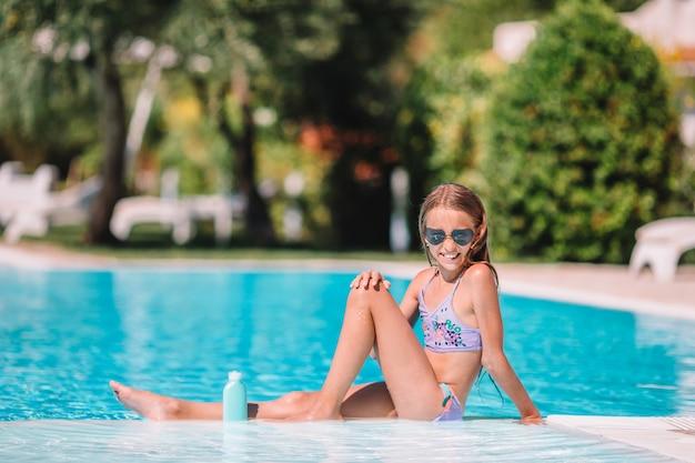 Meisje met zonnescherm in het zwembad Premium Foto