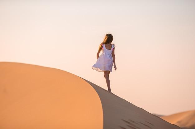 Meisje onder de duinen in de woestijn in de verenigde arabische emiraten Premium Foto