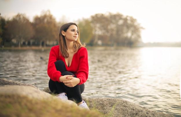 Meisje ontspannen, zittend naast een meer Premium Foto