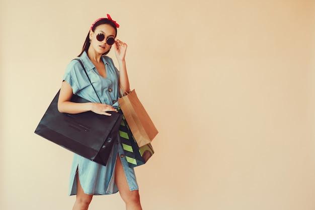 Meisje op een gele muur met boodschappentassen Gratis Foto