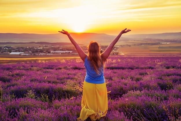 Meisje op een lavendelgebied bij zonsondergang. zonnige zomeravond op de krim. Premium Foto