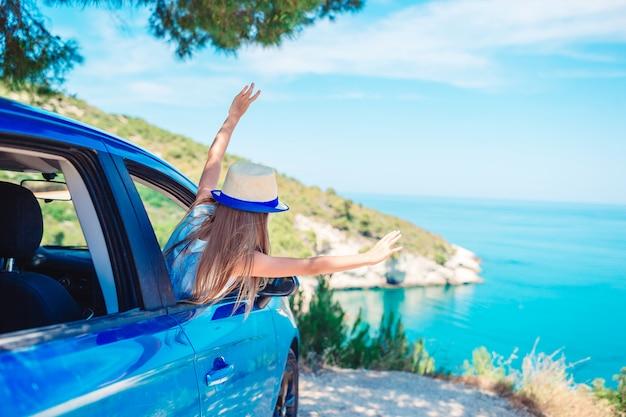 Meisje op vakantiereis met auto op mooi landschap Premium Foto