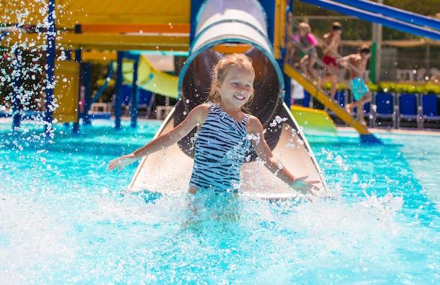 Meisje op waterglijbaan bij aquapark op de zomervakantie Premium Foto