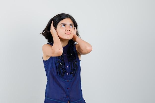Meisje opzoeken terwijl hand in hand op oren in blauwe blouse. Gratis Foto
