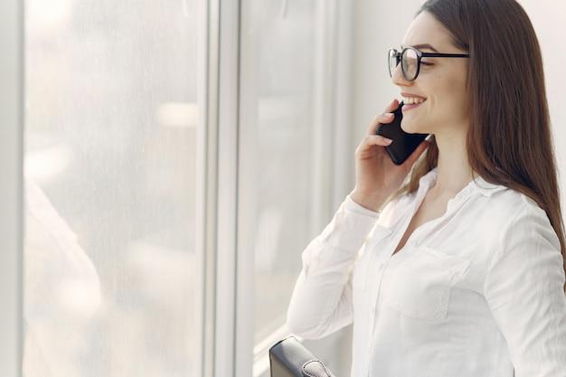 Meisje permanent in het kantoor met een telefoon Gratis Foto