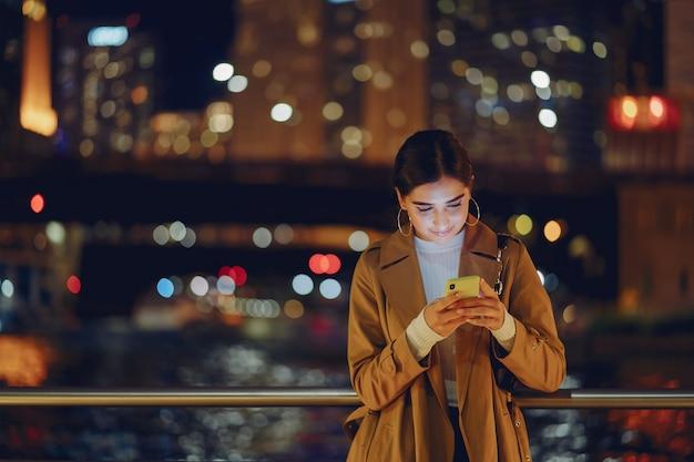 Meisje 's nachts met telefoon Gratis Foto