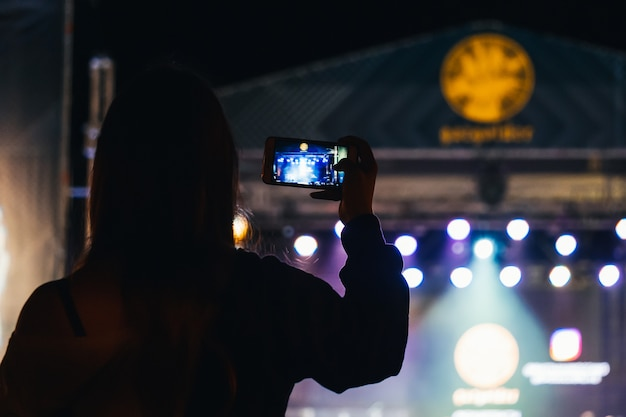 Meisje schiet video op mobiele telefoon tijdens een live concert van muzikant basta Premium Foto