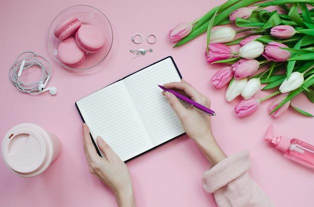 Meisje schrijven verlanglijstje voor toekomstige plannen. platliggende compositie met bloemen, een notitieblok, een kopje koffie en snoep Premium Foto