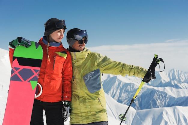 Meisje snowboarder en skiër die van het sneeuwlandschap genieten van bergen in gudauri, georgië Premium Foto