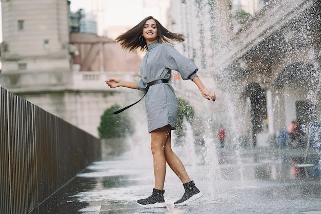 Meisje speelt en danst rond in een natte straat Gratis Foto