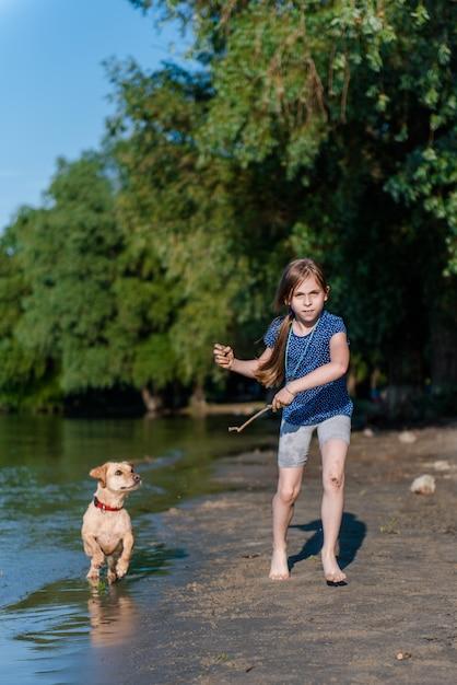 Meisje speelt met haar hond in de rivier Premium Foto