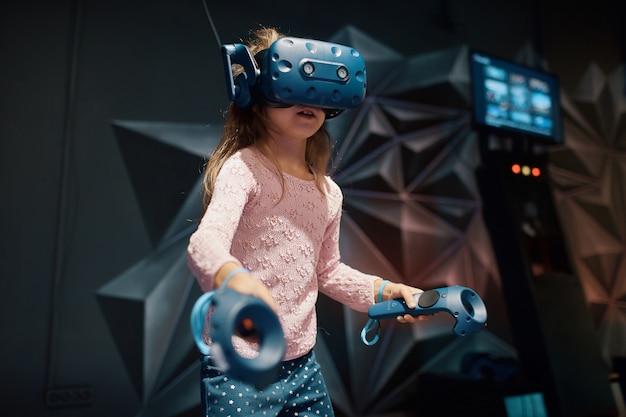 Meisje speelt met virtual reality-bril, houdt controller in haar handen, in de speelkamer Premium Foto