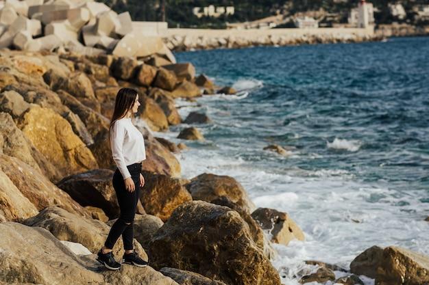 Meisje staat op stenen voor de kust van de cote d'azur in nice, frankrijk Premium Foto