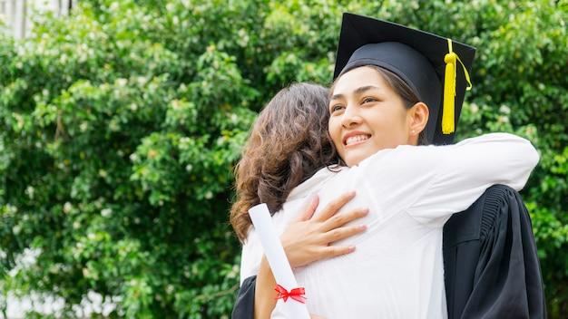 Meisje student met de toga afstuderen en hoed knuffel de ouder in felicitatie ceremonie. Premium Foto