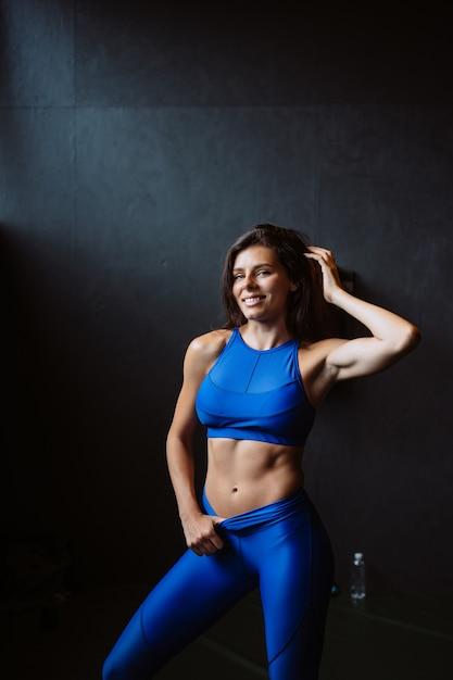Meisje toont haar opgepompte buikpers. atletisch lichaam na dieet en zware inspanning, slanke taille Gratis Foto