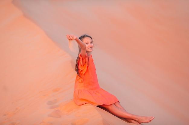 Meisje tussen de duinen in de rub al-khali-woestijn in de verenigde arabische emiraten Premium Foto