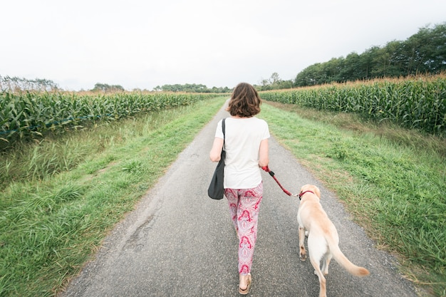 Meisje van achter wordt gezien die onderaan een weg loopt en een hond aan de leiband draagt Premium Foto