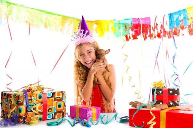Meisje van het partij het blonde jonge geitje gelukkig met aanwezig puppy Premium Foto