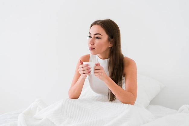 Meisje verblijft in bed en drinkt koffie Gratis Foto