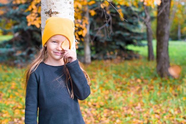 Meisje verstoppertje spelen in de buurt van boom in herfst park Premium Foto
