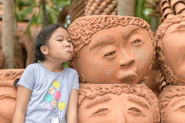 Meisje verveeld of boos emotie tonen in de buurt van klei potten, Premium Foto