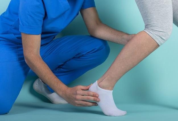 Meisje voert oefeningen met een fysiotherapeut. cyaan muur Premium Foto