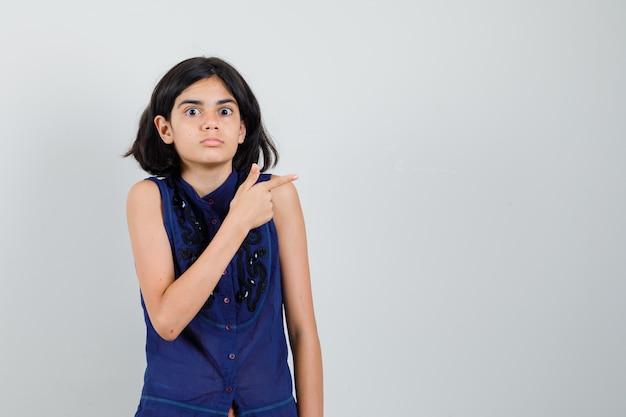 Meisje wijst naar de kant in blauwe blouse en kijkt verbaasd Gratis Foto