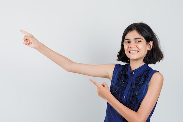 Meisje wijst naar de linkerbovenhoek in blauwe blouse en kijkt joviaal. Gratis Foto