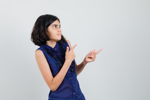 Meisje wijst naar de rechterbovenhoek in blauwe blouse en kijkt gefocust. Gratis Foto