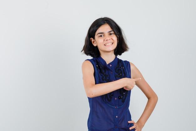 Meisje wijst naar de rechterkant in blauwe blouse en kijkt vrolijk. Gratis Foto