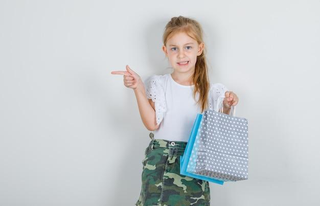 Meisje wijst naar kant met papieren zakken in wit t-shirt Gratis Foto
