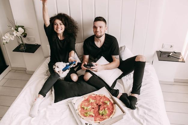 Meisje wint met man op ps op bed spelen Gratis Foto