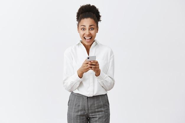 Meisje wordt overweldigd en opgewonden leest ongelooflijk aanbod ontvangen via internet, controleert mailbox in smartphone, kijkt verbaasd, staande over grijze muur in pak Gratis Foto