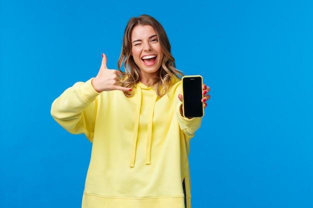Meisje zegt 'hit me up' terwijl ik probeer een hot guy-nummer te krijgen, smartphone vast te houden, mobiele telefoon weer te geven, te knipogen en telefoongebaar te maken, te vragen haar te bellen, staand Premium Foto