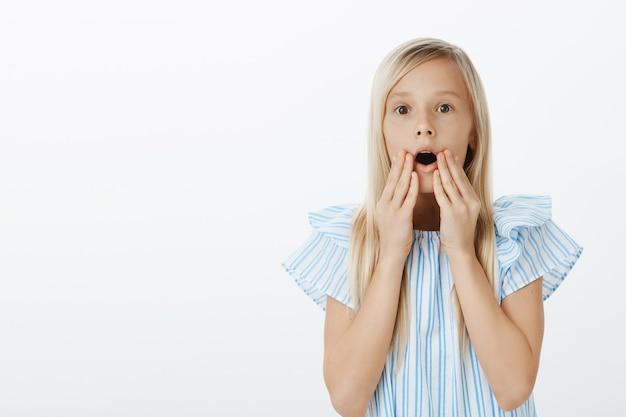 Meisje ziet schattige pop in de winkel en vraagt moeder om hem te kopen. portret van verbaasd en verrast schattige blonde dochter, die kaak laat vallen, wauw zegt en hand in hand in de buurt van geopende mond over grijze muur Gratis Foto
