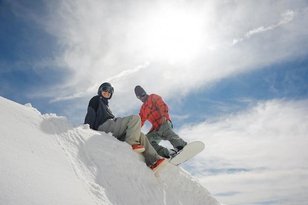 Meisje zit in de sneeuw op de heuvel en de man maakt zich klaar om te gaan snowboarden Premium Foto