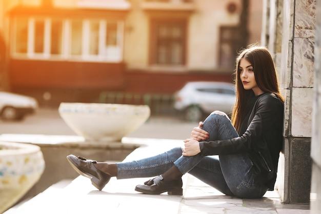 Meisje zitten en leunend op een kolom Gratis Foto