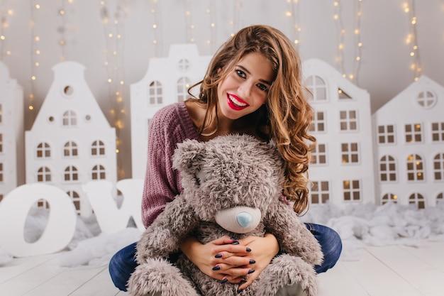 Meisje zittend op de vloer met lichte make-up schattige glimlach en knuffels grijze teddybeer Gratis Foto