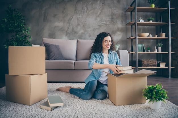 Meisje zittend op de vloer tapijt openen uitpakken haar eigen spullen uitpakken in moderne loft industriële stijl interieur woonkamer Premium Foto