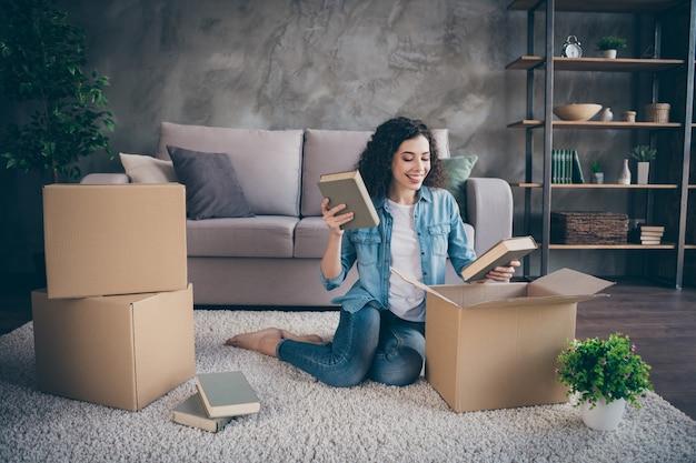 Meisje, zittend op de vloer tapijt verpakking dingen buyings in moderne loft industriële stijl interieur woonkamer Premium Foto