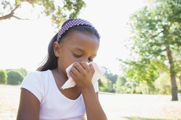 Meisje, zittend op het gras blaast haar neus Premium Foto